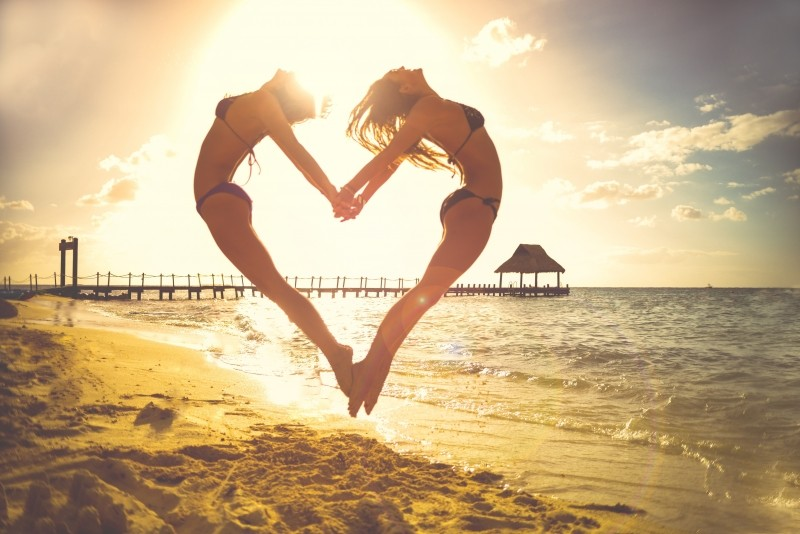 female-friends-jumping-on-beach-holding-hands-in-heartshape-at-sunset[1]