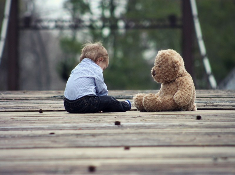 boy-playing-with-teddy-bear-on-wooden-bridge1